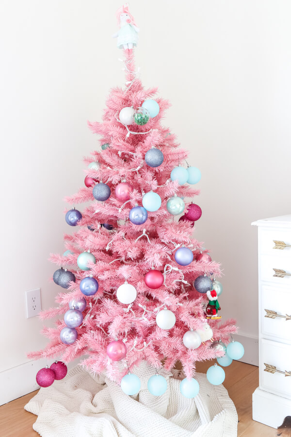 pink christmas tree with colorful ornaments and white lights