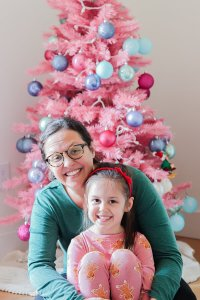 little girl in pink gingerbread pajamas and woman with brown hair and glasses and green shirt sitting in front of decorated pink Christmas tree