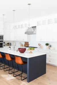white kitchen with navy island and brown leather bar stools