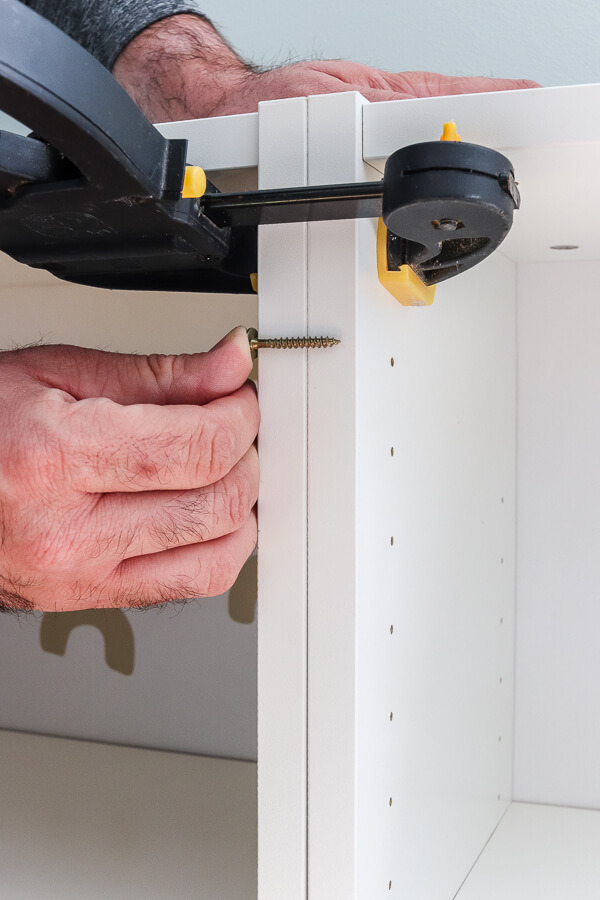 black clamp and man's hand holding screw up to white Ikea billy bookcases