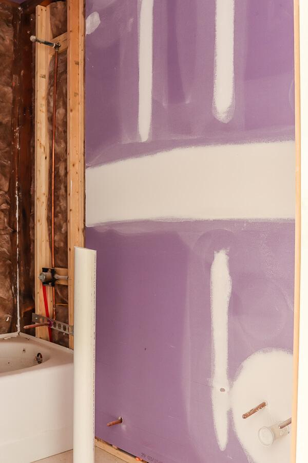 bathtub with purple drywall