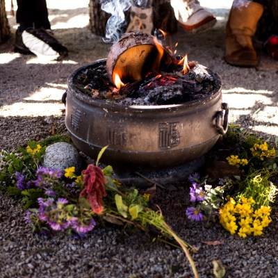 circle of women around a fire with wildflowers all around