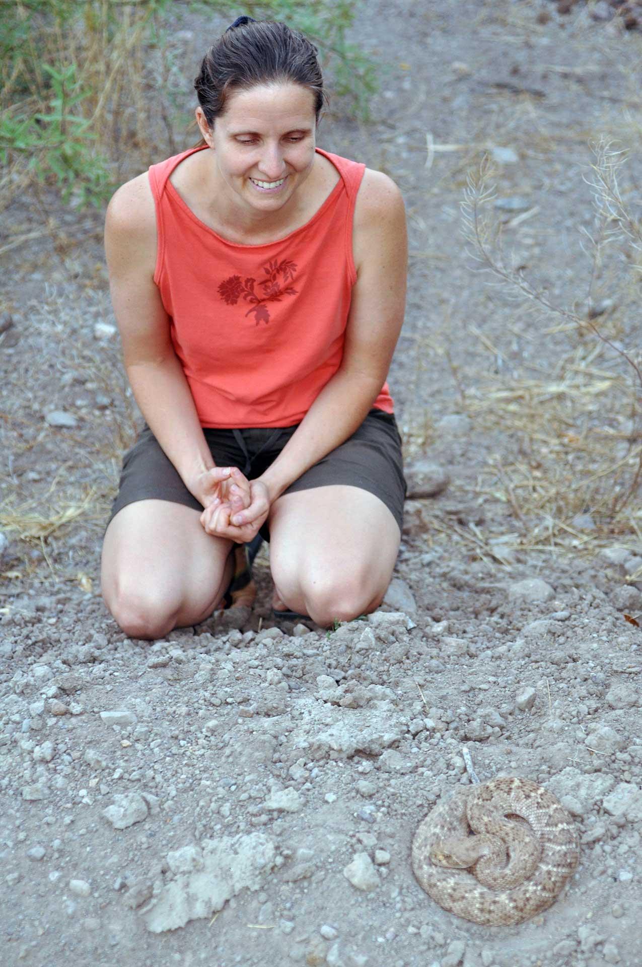 Melissa sitting near Henry, a western diamondback rattlesnake