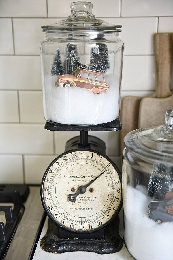 DIY Snow globe jars - A quick & easy Christmas DIY that could be used all winter. Made with ornaments, fake snow, & some trees. These would look amazing on Christmas mantel, table centerpiece, in a kitchen, & so much more.