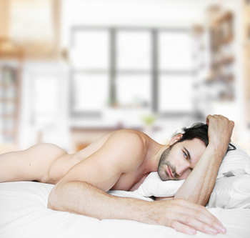 Nude guy in bed alone