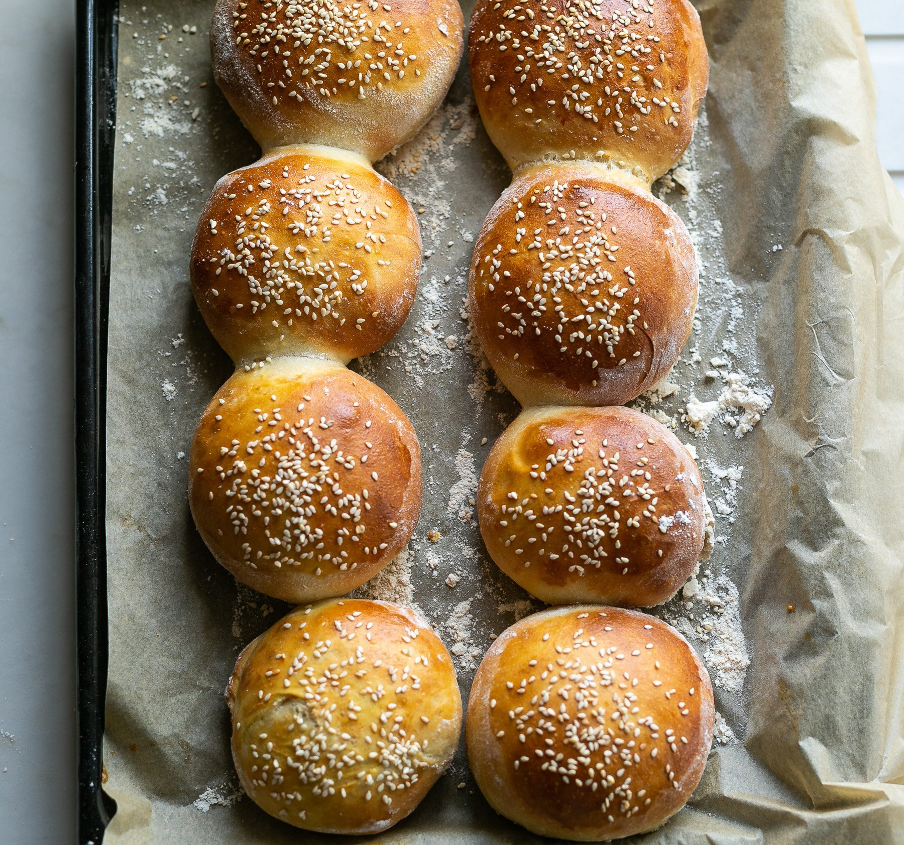 freshly baked brioche burger buns on a baking tray
