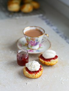Freshly baked fluffy buttermilk scones served with jam and cream and a cup of tea