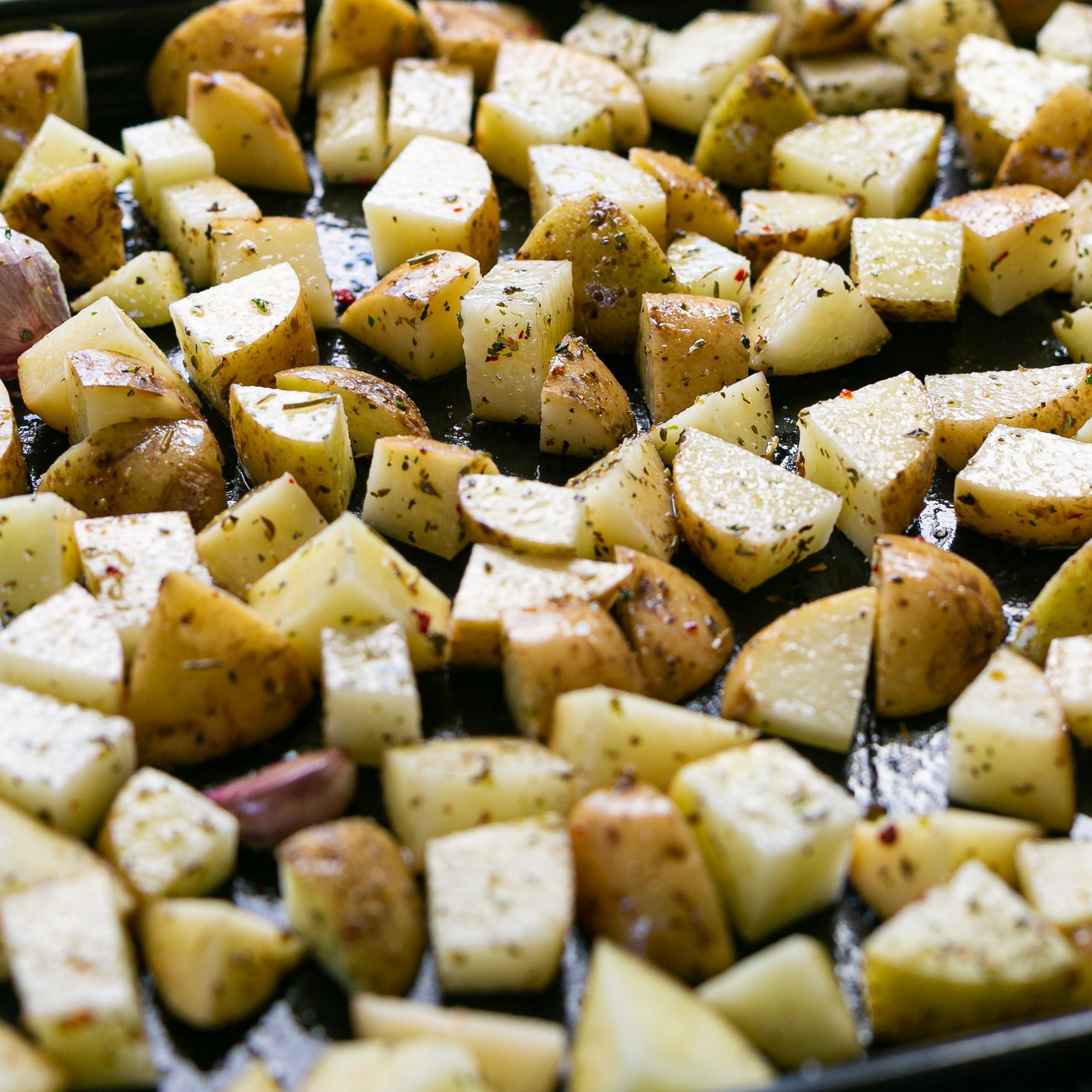seasoned potato pieces on a baking sheet with garlic and oil