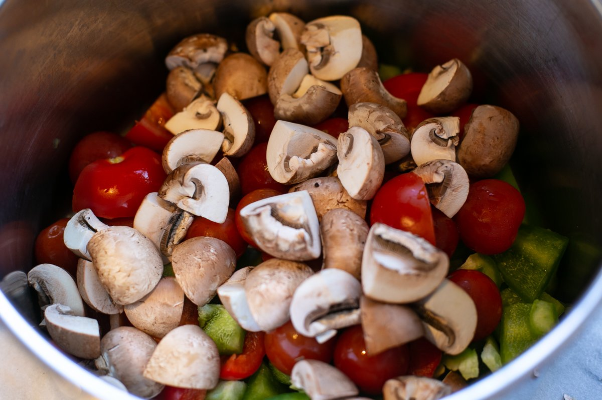 chopped mushrooms, tomatoes and peppers cooking in a pan for homemade lasagne