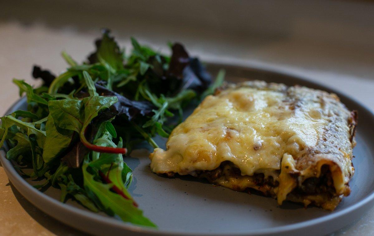 Slice of freshly made homemade lasagne served with salad