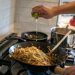 adding lime juice to Chilli Pork Noodles with Peanut Sauce