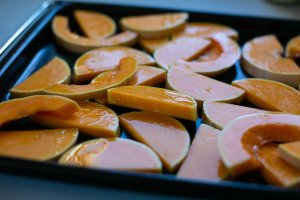 Chopped butternut squash on a baking sheet drizzled with oil