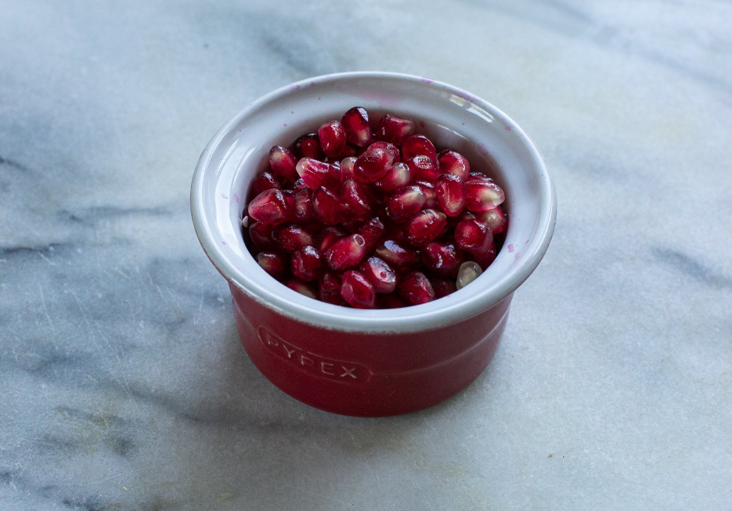 Pomegranate seeds in a ramekin