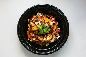 roasted squash with pomegranate and almonds served in a dish