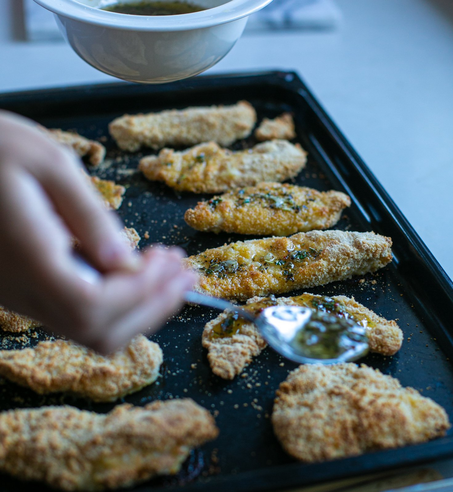 Garlic butter sauce being added to crispy chicken dippers on a baking tray