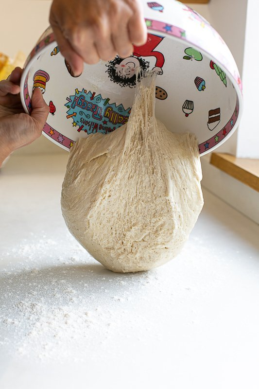 Bloomer dough being tipped onto a floured work surface