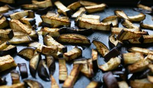 crispy roasted aubergine on a baking tray to be added to pesto pasta