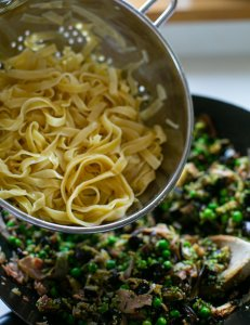 Pasta being added to a pan to cook aubergine pesto pasta