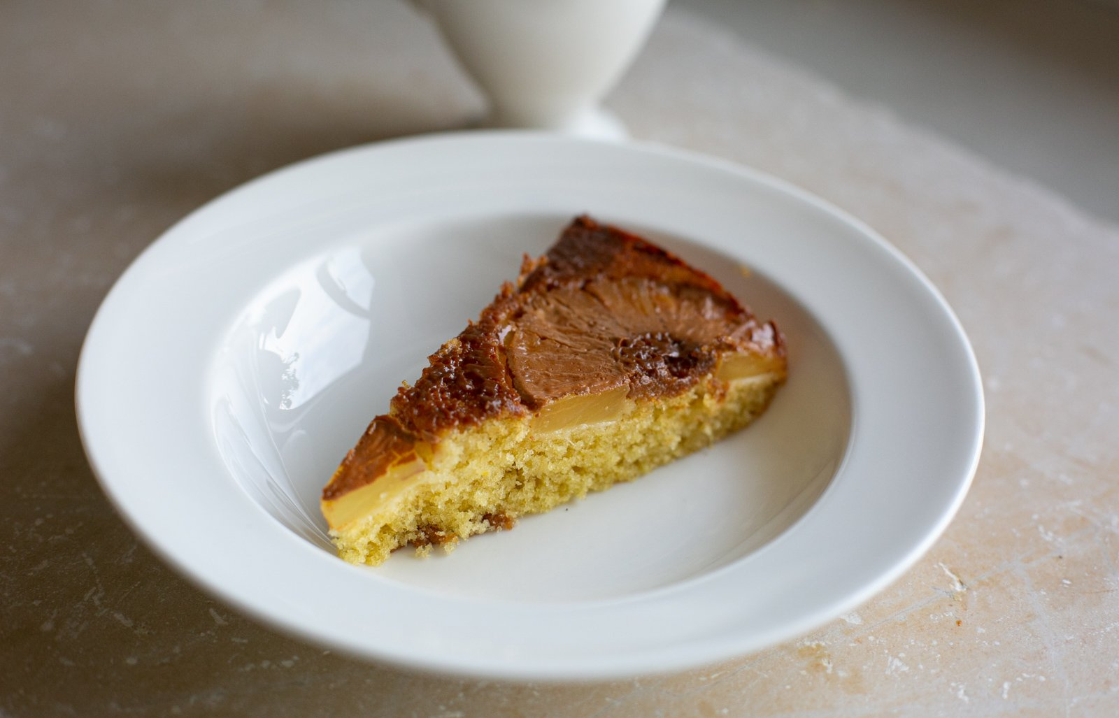 A slice of caramel pineapple summer sponge in a bowl