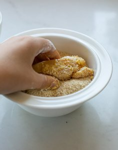 chicken being coated in breadcrumbs ready to bake