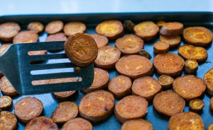 Roasted sweet potato slices on a baking tray being flipped before cooking again