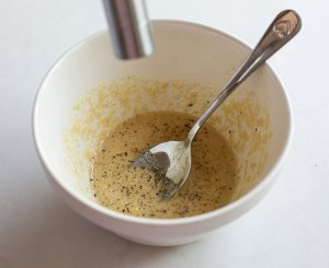 black pepper being added to tahini for baba ganoush