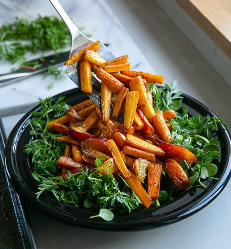carrots and nectarines being added to a bed of salad leaves