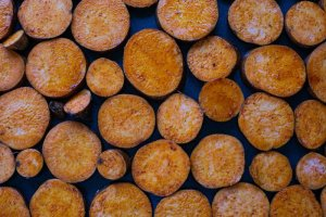 Sweet potato slices on a baking tray coated in oil and paprika