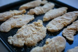 Breaded chicken on a baking tray ready to cook