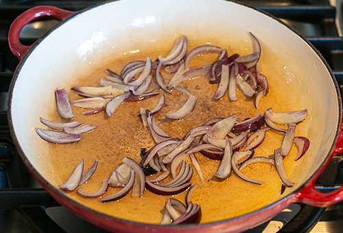 red onions frying in a pan to make special rice