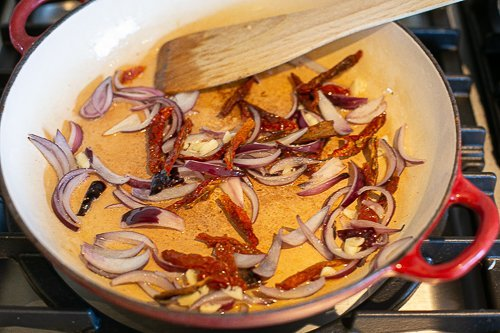 red onions and sun dried tomatoes cooking in a pan to make special rice