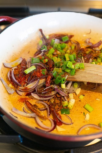 red onions, sun dried tomatoes and spring onions cooking in a pan to make special rice