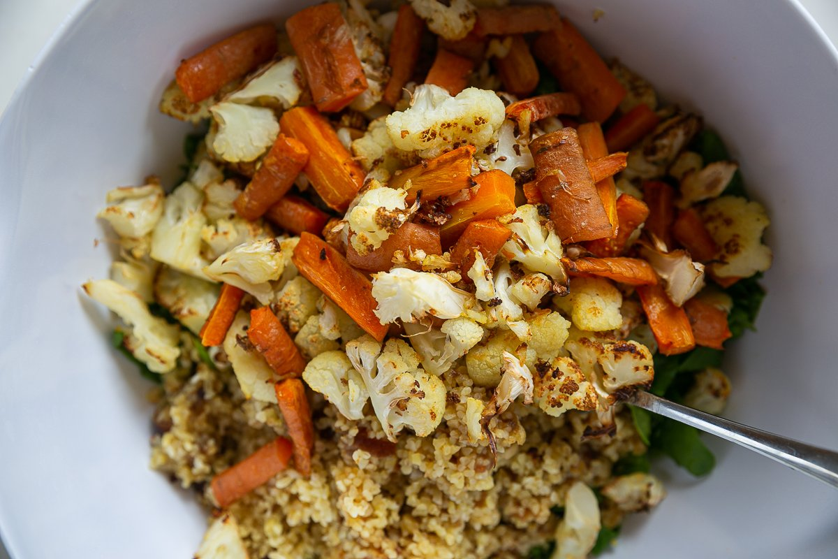 Roasted vegetables, spinach and bulgar wheat in a bowl to mix into a salad