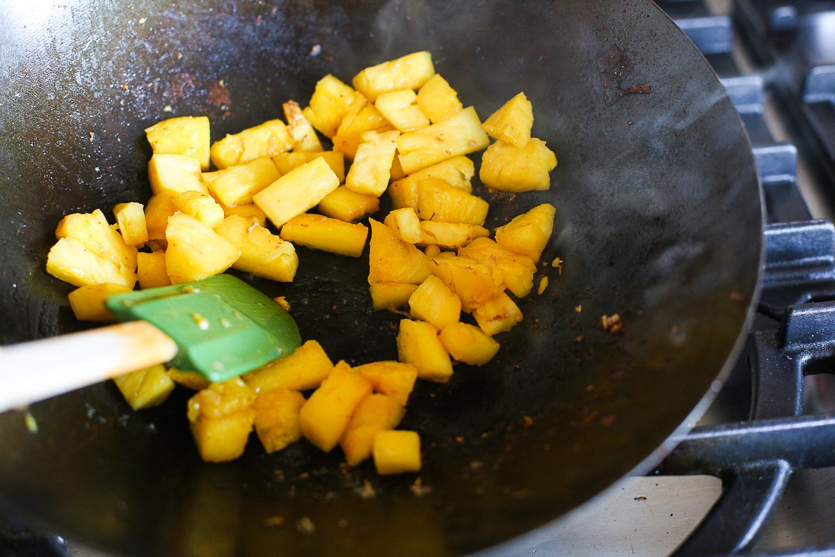 pineapple chunks caramelising in a wok