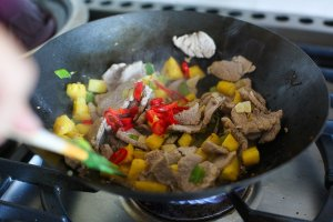 pork and pineapple stir fry cooking in a pan