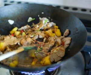 peanut sauce being added to pork stir fry