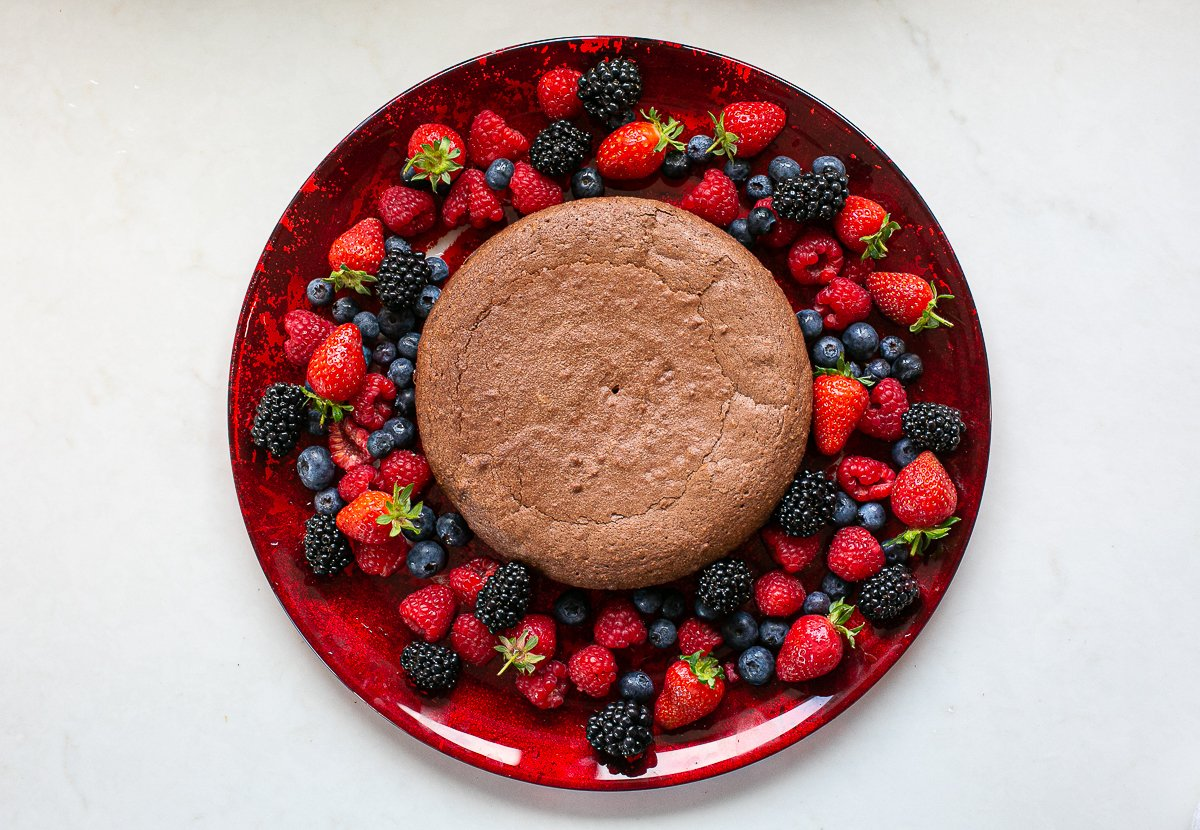 chocolate and amaretti cake served on a plate with fresh berries