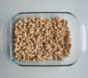 cannellini beans layered across the bottom of an oven safe dish