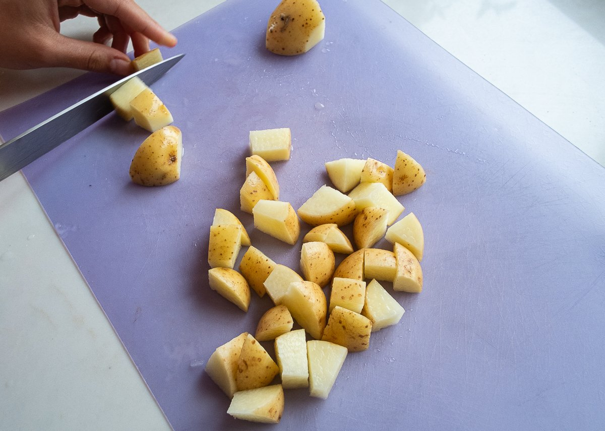 Potatoes being chopped into small pieces on a chopping board