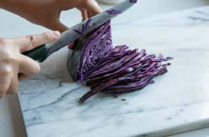 red cabbage being sliced with a knife