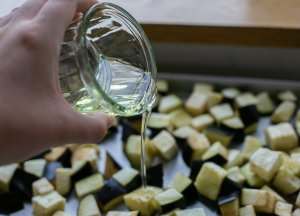 olive oil being poured onto chopped aubergine to roast