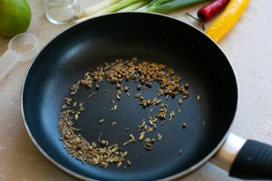 cumin, coriander and fennel seeds toasting in a pan