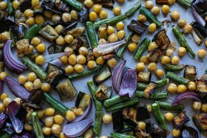 roasted aubergine, chickpeas, green beans and red onions on a baking tray