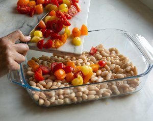 chopped tomatoes being added to cannellini beans in a dish