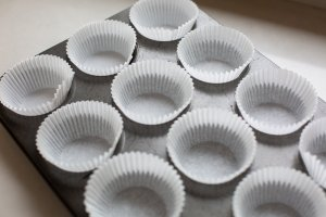 A cupcake tray lined with cases