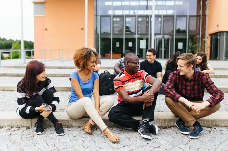 Vier Personen sitzen vor der Hochschulbibliothek auf den Treppenstufen