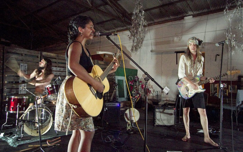Members of the band Weather for Strangers perform during a concert after the grand opening party at KRaP Art (Kimberly's Recycled Art Projects) on Saturday night.