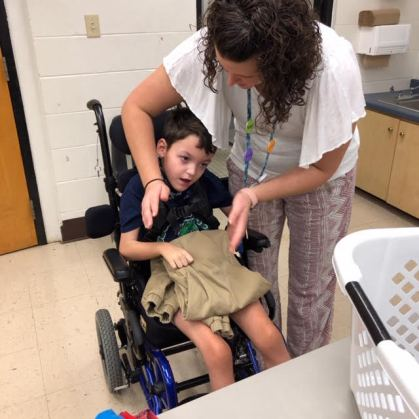 Teacher Brittani Minto helps Tyson Stone fold pants
