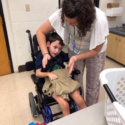 Teacher Brittani Minto helps Tyson Stone fold pants