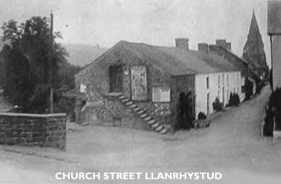 Black and white photo of Church Street Llanrhystud, with village church in the background.